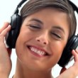 Smiling brunette wearing headphones - Stock Photo