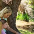 Stock Video: Girl with her daughter on bench