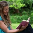 Smiling young woman reading a novel - Stock Photo