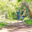 Stock Video: Rear view of father and son walking