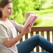 Stock Video: Womreading novel while sitting on bench