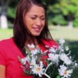 Stock Video: Cheerful womholding white flowers