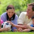 Smiling family trying to catch a soccer ball — 图库视频影像