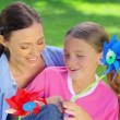 Mother and daughter holding pinwheels — Vídeo de stock