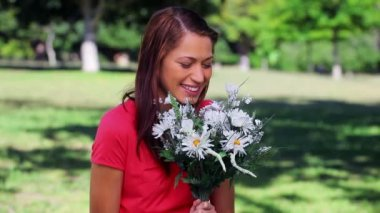 Happy woman laughing while holding flowers — Stock Video
