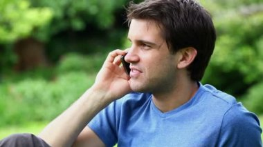 Smiling man sitting while calling — Stock Video