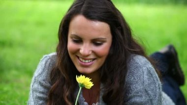 Smiling brunette smelling a yellow flower — Stock Video