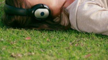 Kadın bir parkta müzik dinlemek — Stok video