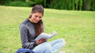 Smiling brunette attentively reading a book — Stock Video