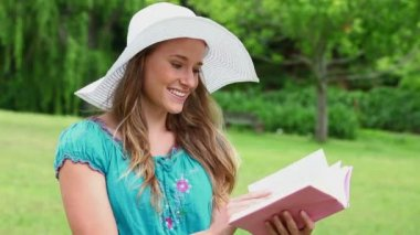 Happy young woman reading a fascinating book — Stock Video