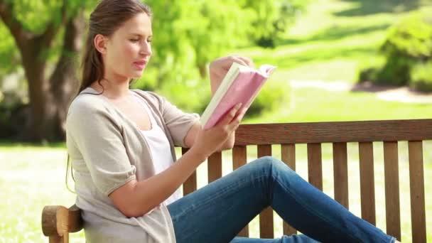 Mujer leyendo una novela mientras estaba sentado en un banco — Vídeo de stock