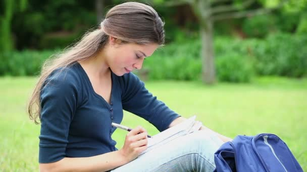 Mujer sonriente escribiendo en un cuaderno — Vídeo de stock