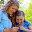 Mother and daughter using a magnifying glass — Vídeo de stock