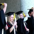 Stock Video: Graduates are passing he tassel from right to left
