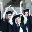 Stock Video: Happy graduates raising arms and jumping