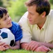 Happy father and son lying on the grass with a soccer ball - Foto Stock