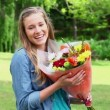 Happy young woman smelling flowers — Stock Video #21635259