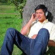 Stock Video: Peaceful mleaning against tree while listening to music