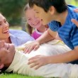 Smiling man lying on the grass with his family — Vídeo Stock