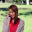 Stock Video: Smiling brunette womusing mobile phone