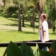 Woman walking out on decking — Stock Video