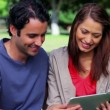 Stock Video: Smiling couple looking at tablet pc
