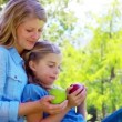 Daughter and mother holding apples — Vídeo Stock