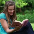 Stock Video: Smiling womreading fascinating novel