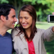 Smiling couple taking a picture of themselves — Stock Video #21638781