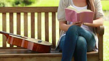 Mujer leyendo un libro con una guitarra al lado de ella — Vídeo de stock