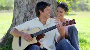 Laughing man een gitaar spelen voor zijn vriendin — Stockvideo