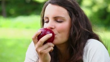 Joyful woman eating a red apple — Stock Video