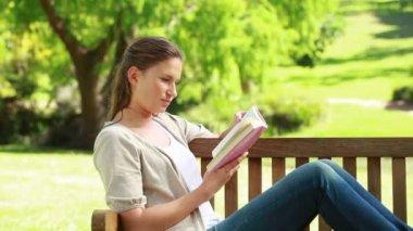 Uma mulher segurando um livro enquanto está sentado em um banco — Vídeo stock