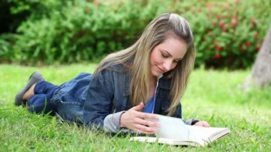 блондинка женщина, читая роман — Стоковое видео