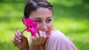 Happy brunette woman holding a pink flower — Stock Video
