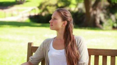 Genç kadın bir bank üzerinde rahatlatıcı — Stok video