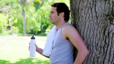 Athletic man drinking water while leaning against a tree — Stock Video