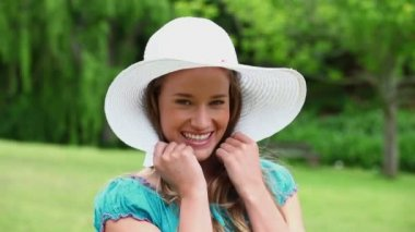 Cheerful young woman holding her hat brim — Stock Video