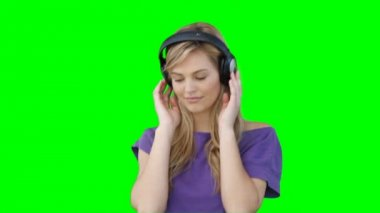 A woman moving to the music on her headphones in front of a green background