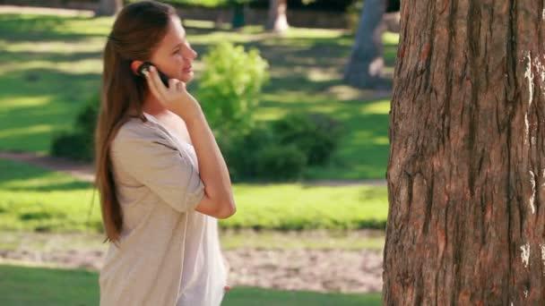 Mujer sonriente a colgar su teléfono móvil — Vídeo de stock
