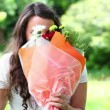 Stock Video: Smiling brunette holding bunch of flowers