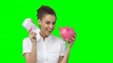 A woman holding up a piggy-bank and a fan of cash as she smiles — Stock Video