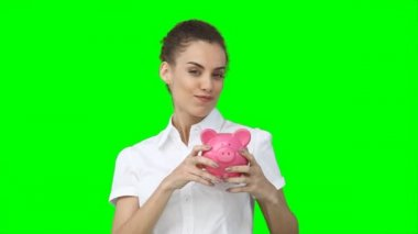 A woman holding her piggy-bank in her hands as she shakes it — Stock Video