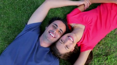 Smiling couple lying on the grass while enjoying the nature — Stock Video