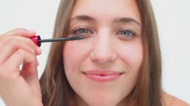 Joyful brunette applying mascara on her eyelashes — Stock Video
