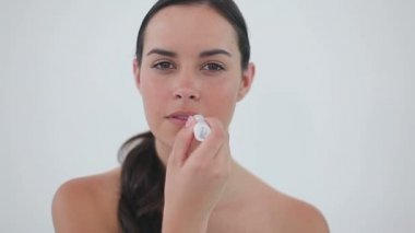 Happy woman putting lip balm on her lips — Stock Video
