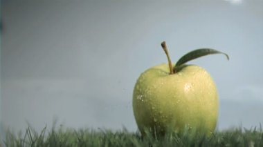 Apple in super slow motion put on the lawn — Wideo stockowe