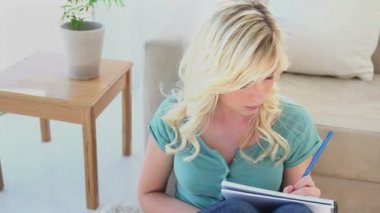 Young blonde woman writing in a notebook — Stock Video