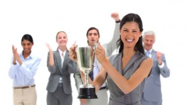 Woman holding a trophy with co-workers applauding — Stock Video