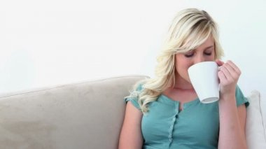 Blonde haired woman drinking coffee — Stock Video